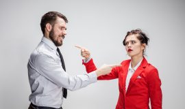 Two corporate professionals are pictured. They have exaggerated body language, suggesting that they are having difficult conversations. This image aims to visualise the topic of the blog which describes why difficult conversations might go wrong and how to overcome this with effective communication.